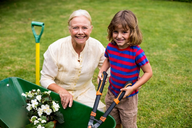 Boy with granny holding scissors over wheelbarrow at yard