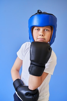 A boy with green eyes wearing a boxing helmet and gloves on a blue background