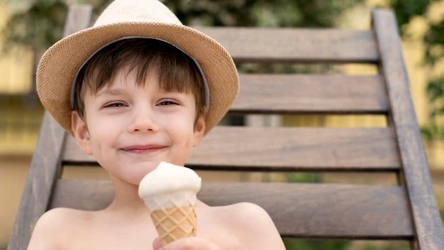 ベッドの太陽の上に座っている間アイスクリームを食べる帽子の少年