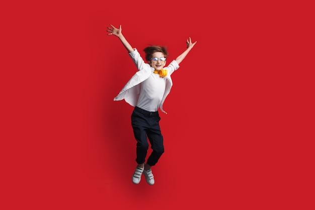 ヘッドフォンを持った少年がジャンプしています