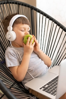 Boy with headphones and laptop enjoying apple