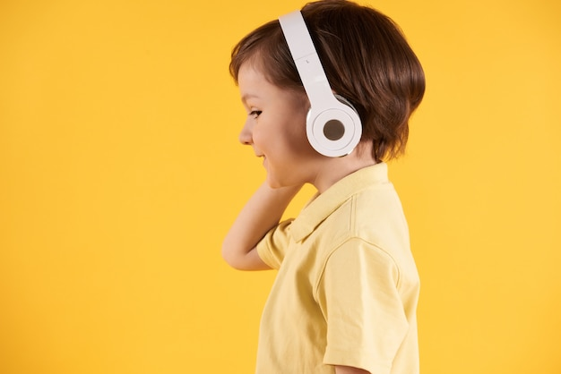 Boy with headphones listens to music side view.