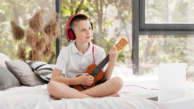 Boy with headphones playing ukulele long shot