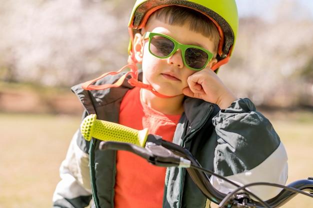 Мальчик с шлемом езда на велосипеде