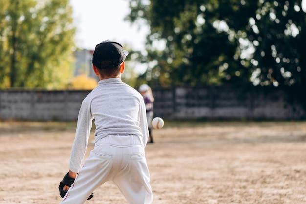 Boy with his back turned stands preparing to catch a ball while playing baseball
