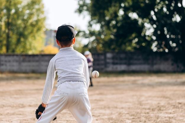 野球をしながらボールをキャッチする準備をして、背を向けた少年