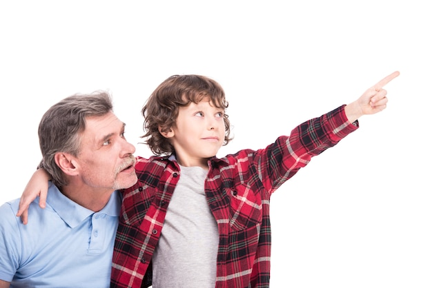 Boy with his grandpa, is pointing somewhere by hand.