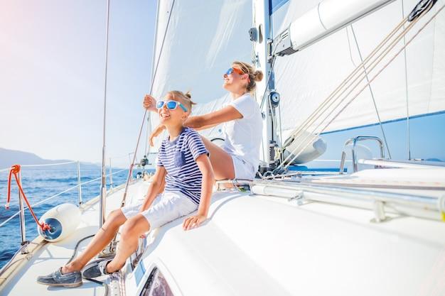 Мальчик с сестрой на борту парусной яхты в летнем круизе. путешествие, приключение, яхтинг с ребенком на семейном отдыхе.