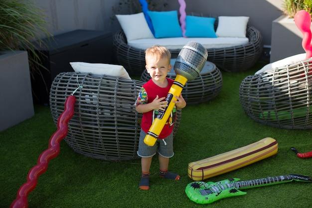 インフレータブルマイクを持つ少年。夏のインフレータブルおもちゃ