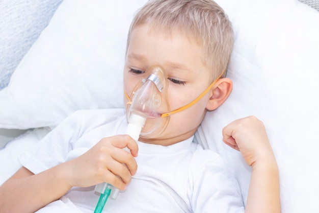 Boy with an inhaler mask. respiratory problems in asthma. boy with an inhaler mask lies in bed and breathes adrenaline.