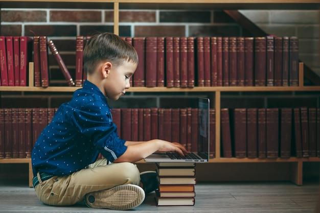 Мальчик с ноутбуком и книгами