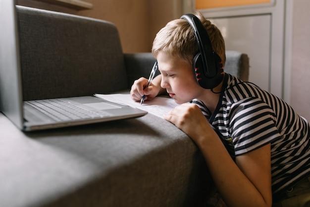 ヘッドフォンで宿題をしているラップトップを持つ少年