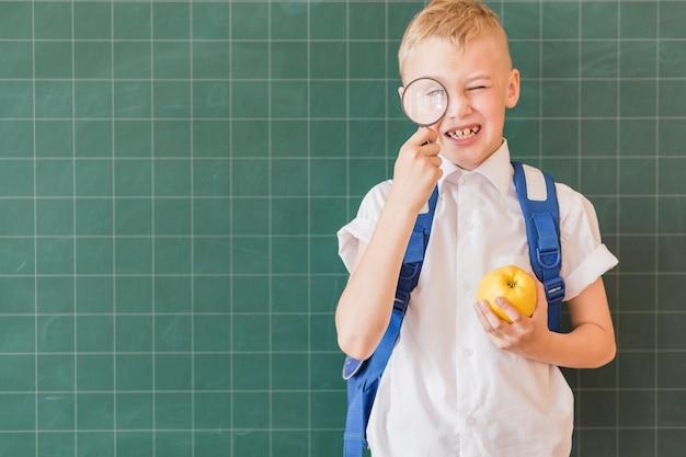 Мальчик с лупой и рюкзаком возле доски