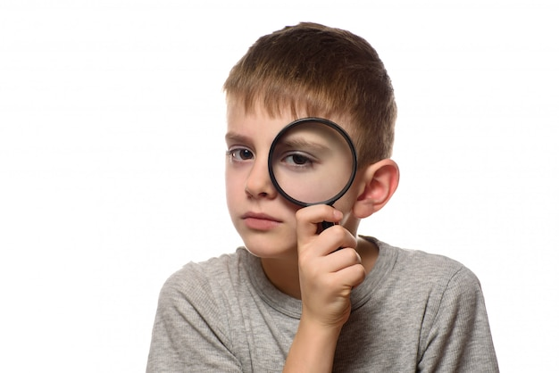Boy with a magnifying glass in his hands. little explorer. white