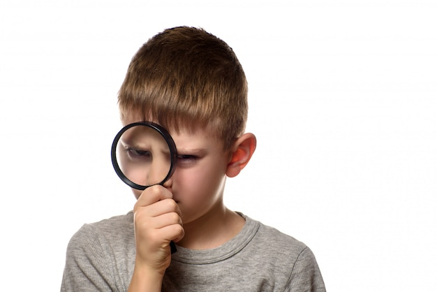 Boy with a magnifying glass in his hands