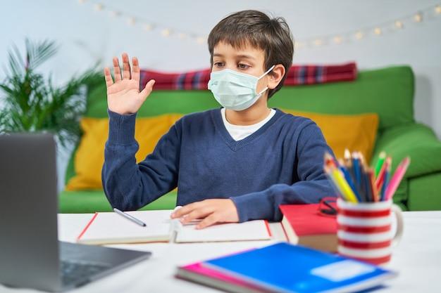 Мальчик в маске проводит видеоконференцию на ноутбуке с учителем из дома, в наушниках и машет рукой на экране, свободное место