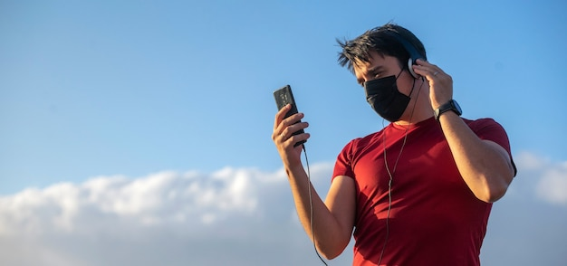 Мальчик с наушниками маски и смартфоном, слушающим музыку на природе