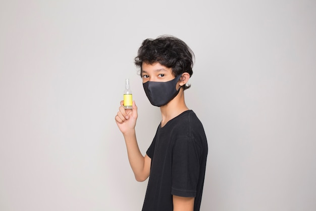Boy with mask holding a hand sanitiser