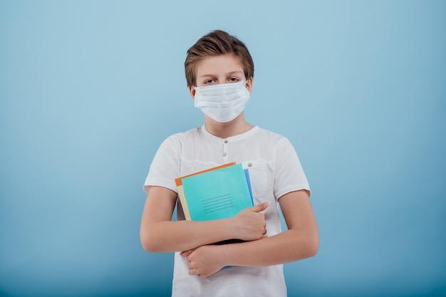 의료 마스크를 쓴 소년은 파란색 배경에 격리된 노트북과 책을 손에 들고 있습니다.