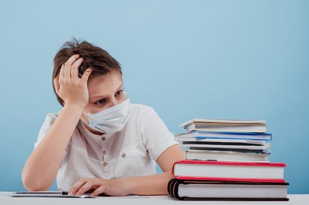의료 마스크를 쓴 소년은 파란 배경에 격리된 테이블에 앉아 있는 것이 지겹다는 것을 배운다