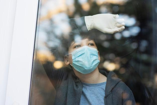 Мальчик с медицинской маской, глядя на улицу