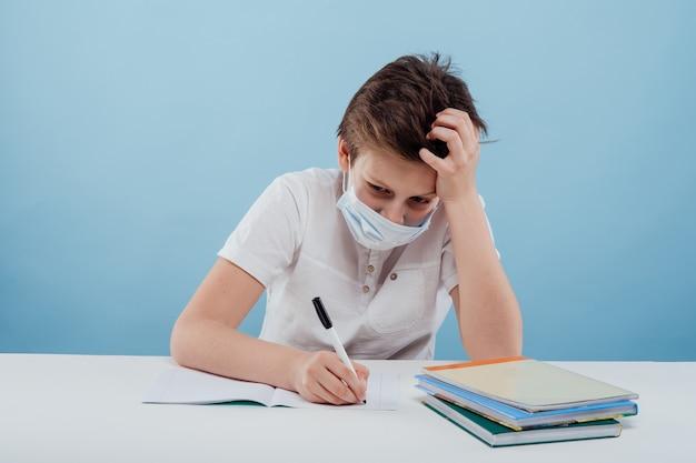 의료 마스크를 쓴 소년은 파란색 배경에 격리된 탁자에 앉아 있는 공책에 글을 씁니다.
