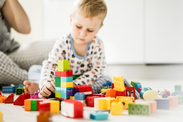 Boy with mom playing in colorful building kit