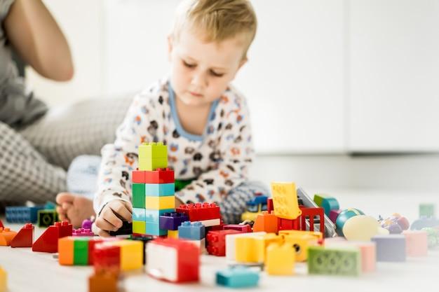 カラフルな建物のキットで遊んでいるママと少年
