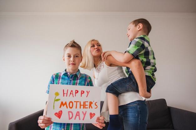 彼の兄弟と彼の母親とバックグラウンドで母の日のポスターと少年