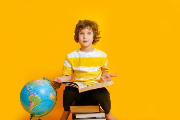 Мальчик со старыми книгами Premium Фотографии