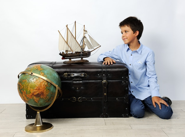 Boy with old globe and ship