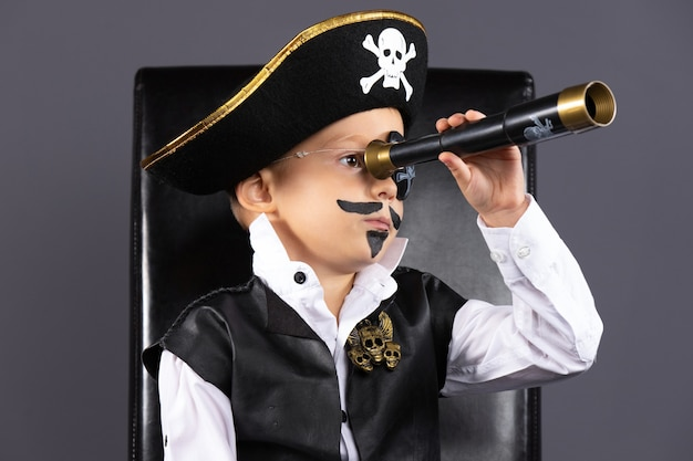 A boy with a painted face sits on a black leather armchair. he is disguised as a pirate. halloween concept.