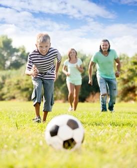 Ragazzo con i genitori che giocano con pallone da calcio