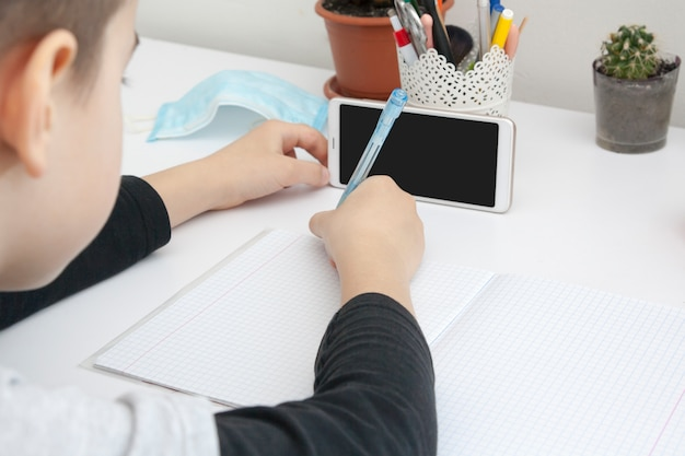 A boy with a pen and notebook at the desk on distance learning with a smartphone app