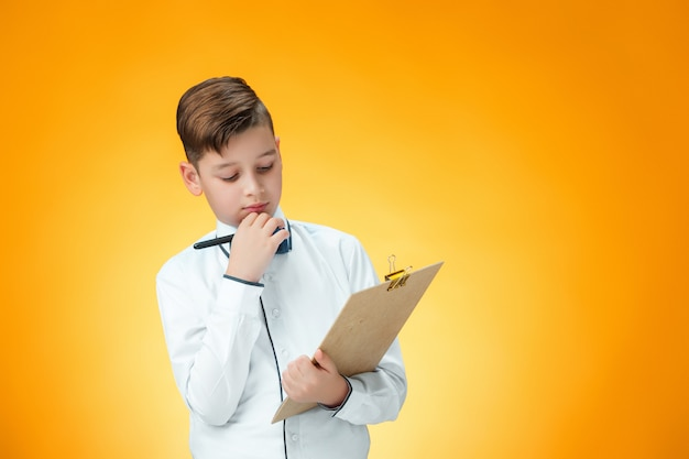 The boy with pen and tablet for notes
