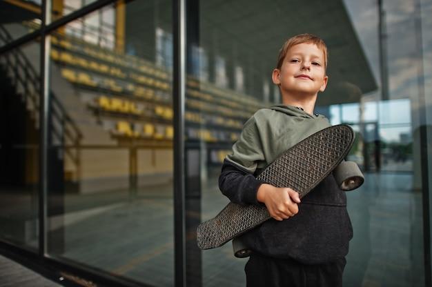 スタジアムで手にペニーボードを持つ少年。