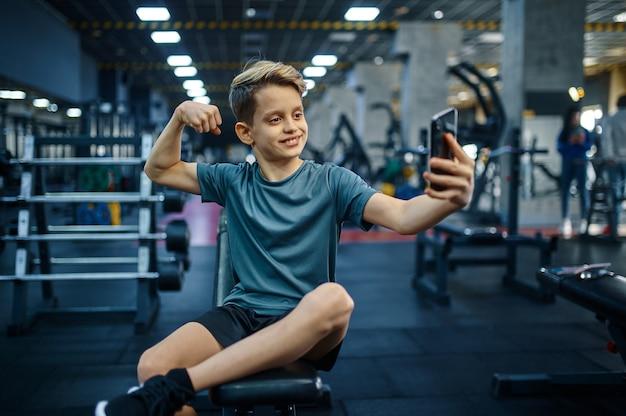 전화 소년은 체육관에서 벤치에 selfie를 만든다. 스포츠 클럽, 건강 관리 및 건강한 라이프 스타일 훈련, 운동 모범생