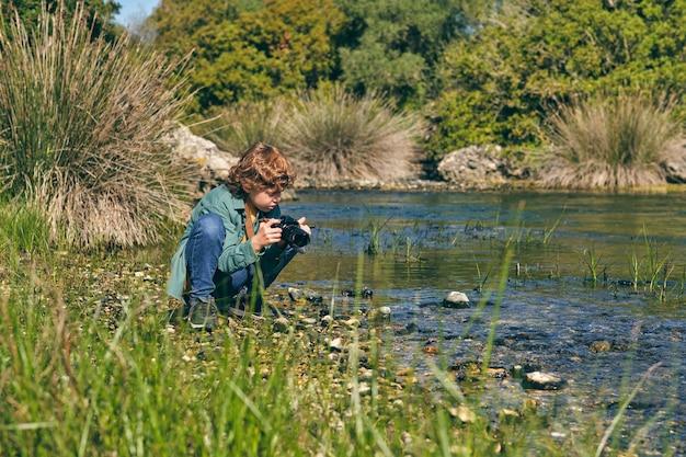 강 근처 잔디 해안에 앉아 사진 카메라와 소년