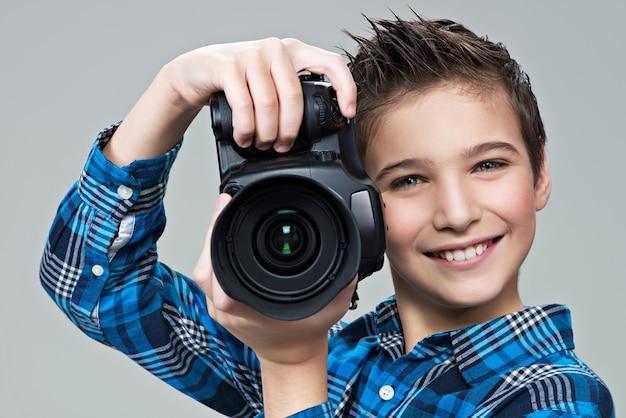 Ragazzo con la macchina fotografica che cattura le immagini. ritratto del ragazzo caucasico con fotocamera digitale nelle mani