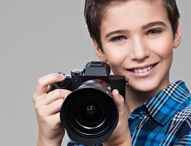 写真を撮る写真カメラを持つ少年。手にデジタルカメラを持つ白人の少年の肖像画