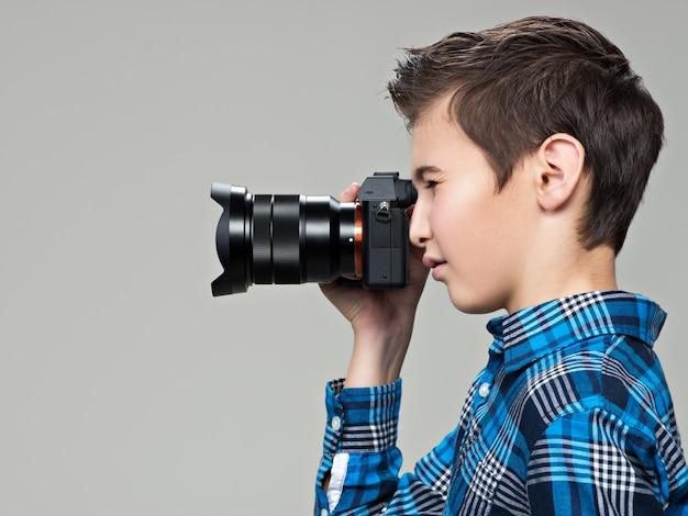写真を撮る写真カメラを持つ少年。デジタル一眼レフカメラで撮影している10代の少年。プロフィールポートレート
