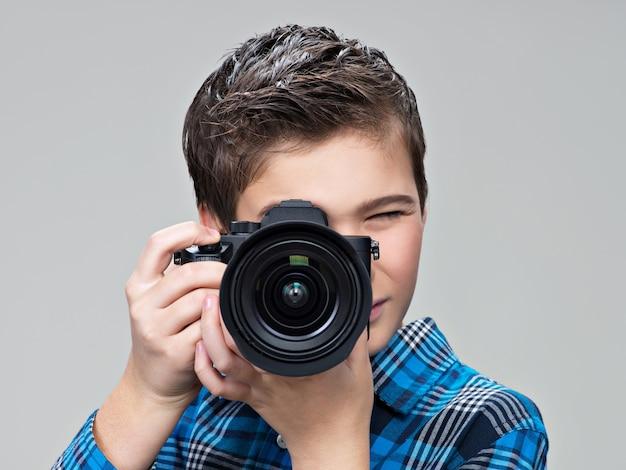 写真を撮る写真カメラを持つ少年。デジタル一眼レフカメラの写真を撮るティーンエイジャーの少年