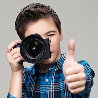 写真を撮る写真カメラを持つ少年。デジタル一眼レフカメラを持つティーンエイジャーの少年は親指を上に表示します