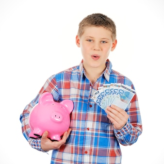 Boy with piggy bank and banknote on white space