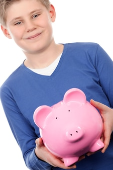 Boy with pink piggybank on white space