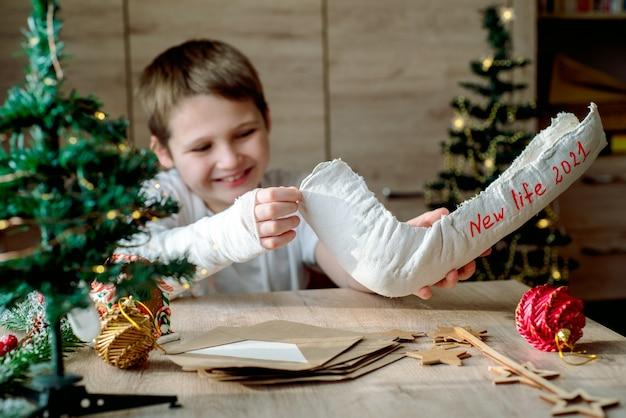 그의 팔에 석고 캐스트를 가진 소년은 크리스마스 공예품을 만듭니다. 손 골절 및 부상. 석고 모형을 제거하고 새로운 삶을 기다립니다. 새해와 새로운 계획.