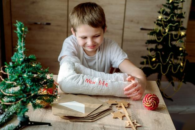 그의 팔에 석고 캐스트를 가진 소년은 크리스마스 공예품을 만듭니다. 손 골절 및 부상. 석고 모형을 제거하고 새로운 삶을 기다립니다.