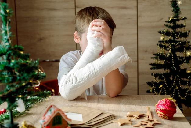 그의 팔에 석고 캐스트를 가진 소년은 크리스마스 공예품을 만듭니다. 손 골절 및 부상. 석고 캐스트 제거