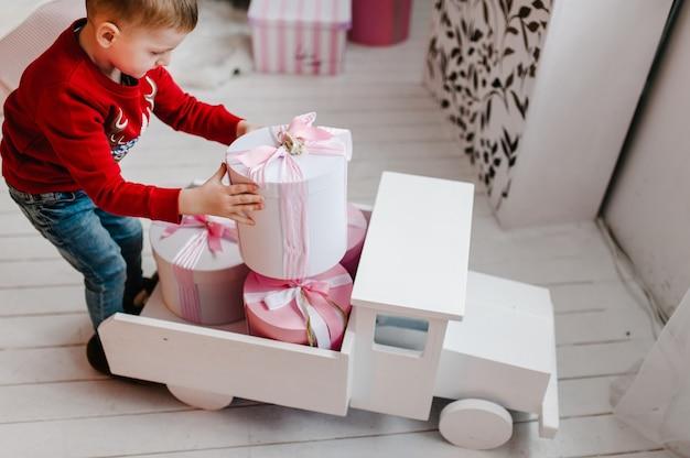 Мальчик с подарками подарки с новым годом и рождеством христовым оформлен интерьер