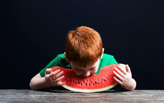 붉은 머리를 가진 소년이 덩어리로 자른 붉은 육즙 수박을 물다.